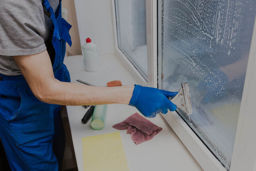 man cleaning window using small tool