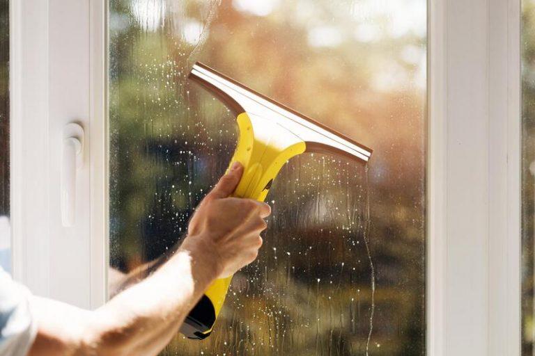 man cleaning window using tool